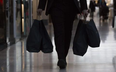 A shopper carries bags from inside the Westfield London shopping centre - Credit: Bloomberg