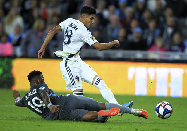 LA Galaxy midfielder Uriel Antuna (18) has the ball deflected by Minnesota United defender Romain Metanire (19) during the first half of an MLS soccer first-round playoff match, Sunday, Oct. 20, 2019, in St. Paul, Minn. (AP Photo/Andy Clayton-King)