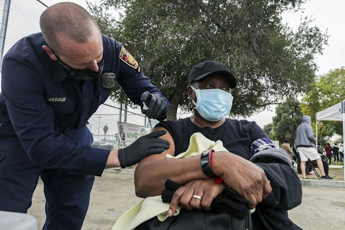 L.A. firefighter Jason Jasgur administers a COVID-19 vaccine to Althea Darby, 69, at a mobile vaccination site in South L.A.