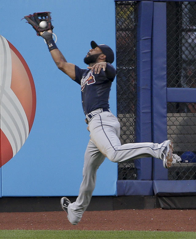 Atlanta Braves right fielder Jason Heyward (22) leaps to catch a ball hit deep by New York Mets' Eric Young Jr. in the second inning of a baseball game, Tuesday, July 8, 2014, in New York. (AP Photo/Julie Jacobson)