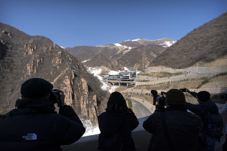 Journalists take photos of the National Alpine Skiing Center in Yanqing on the outskirts of Beijing, Friday, Feb. 5, 2021. Beijing Olympic organizers showed off the downhill skiing venue and the world's longest bobsled and luge track Friday, one year ahead of the scheduled opening of the 2022 Olympic Winter Games. (AP Photo/Mark Schiefelbein)