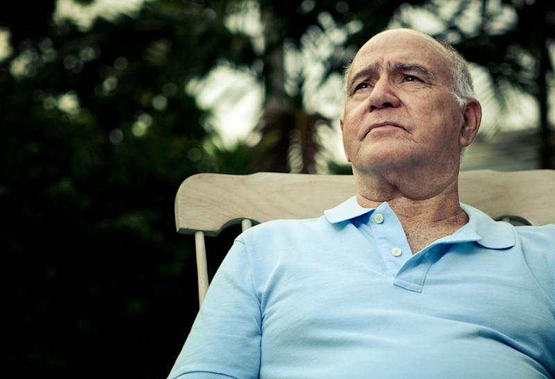 Older man sitting in a rocking chair outside and looking upward.