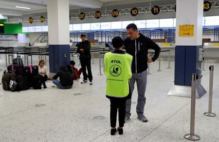 An ATOL official assists passengers at Manchester Airport