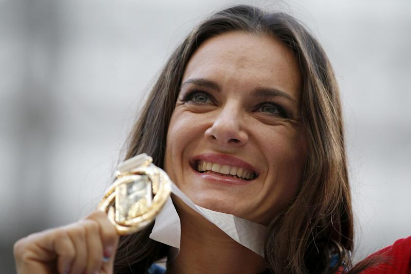 Russia's Yelena Isinbayeva poses with her gold medal in the women's pole vault as she stands on the podium during the medal ceremony at the World Athletics Championships in the Luzhniki stadium in Moscow, Russia, Thursday, Aug. 15, 2013. (AP Photo/Alexander Zemlianichenko)