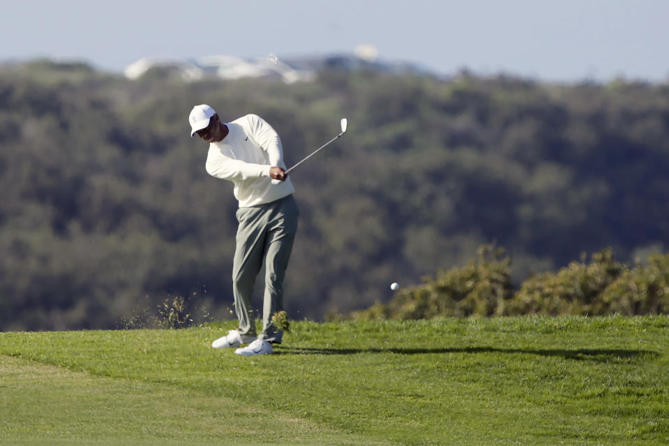 Tiger Woods plays his second shot from the 13th fairway on the Torrey Pines South Course during the second round of The Farmers Insurance golf tournament in San Diego, Friday, Jan. 24, 2020. A police officer working crowd control accepted a bet against Tiger and handed the $20 winnings to a young boy. (AP Photo/Alex Gallardo)