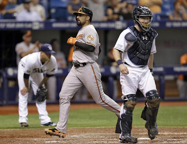 Baltimore Orioles' Nick Markakis, center, scores between Tampa Bay Rays starting pitcher Alex Cobb, left, and catcher Ryan Hanigan, right, on a double by Orioles Steve Pearce during the fifth inning of a baseball game Wednesday, June 18, 2014, in St. Petersburg, Fla. (AP Photo/Chris O'Meara)