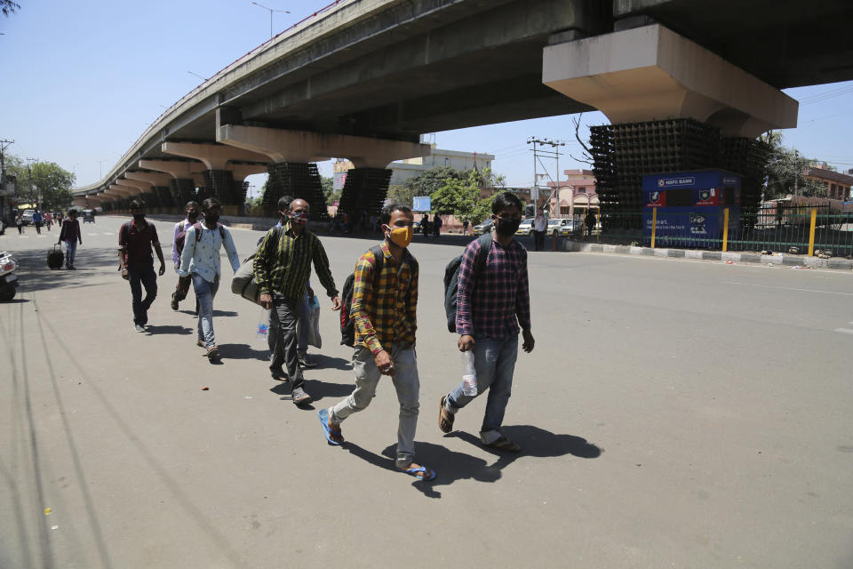 Migrant laborers from other states walk through a deserted road during a curfew as a precautionary measure against COVID-19 in Jammu, India, Sunday, April.25, 2021. (AP Photo/Channi Anand)
