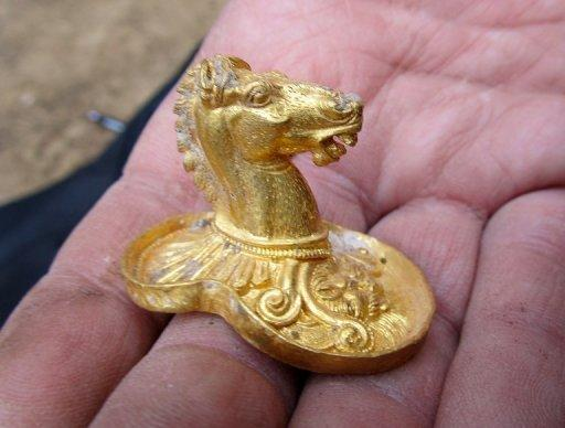 An archaeologist holds a golden horse's head, part of an ancient treasure trove unearthed near a Bulgarian village