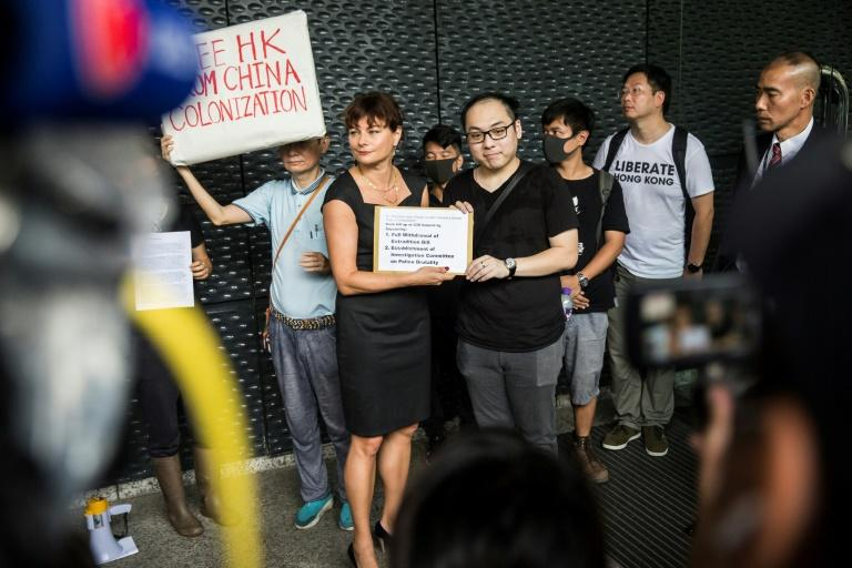 A protester hands a petition to a representative of the European Union at their Hong Kong office