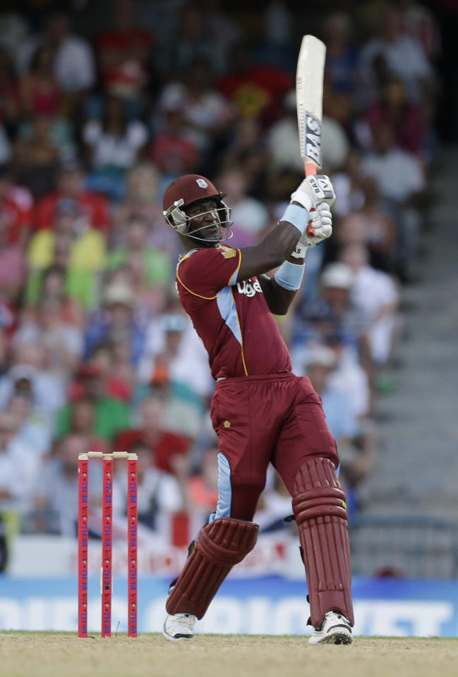 West Indies' Darren Sammy hits a six off England's Jade Dernbach during their second T20 International cricket match at the Kensington Oval in Bridgetown, Barbados, Tuesday, March 11, 2014. West Indies won by 5 wickets with 7 balls remaining. (AP Photo/Ricardo Mazalan)
