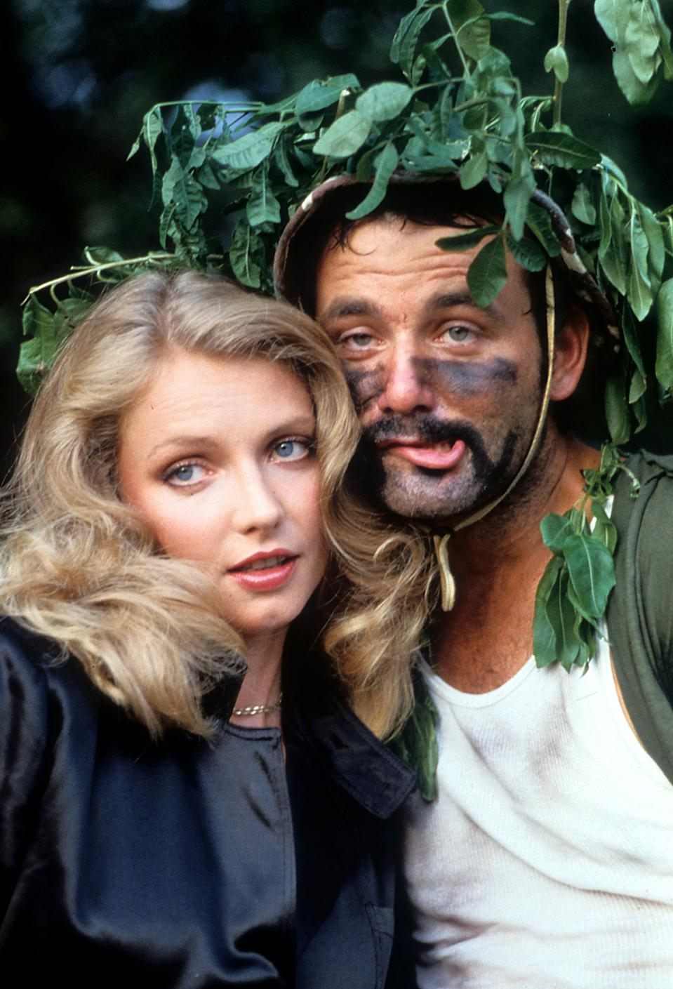 Cindy Morgan and Bill Murray nestled behind a tree in a scene from the film 'Caddyshack', 1980. (Photo by Orion Pictures/Getty Images)