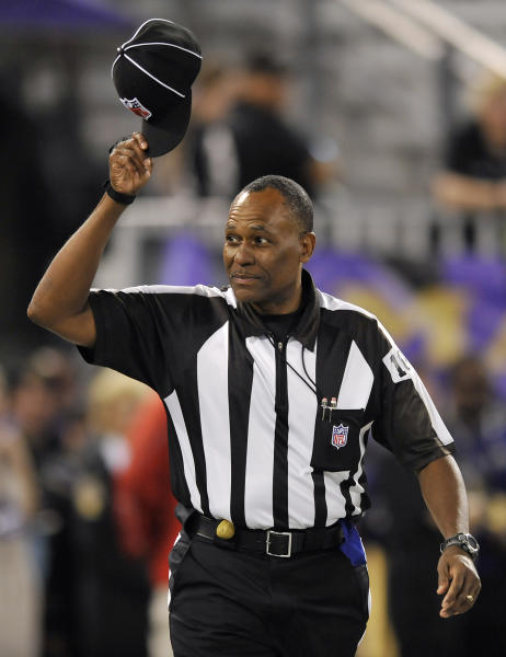 Head linesman Wayne Mackie tips his cap as he walks on the field before an NFL football game between the Baltimore Ravens and Cleveland Browns in Baltimore, Thursday, Sept. 27, 2012. (AP Photo/Gail Burton)