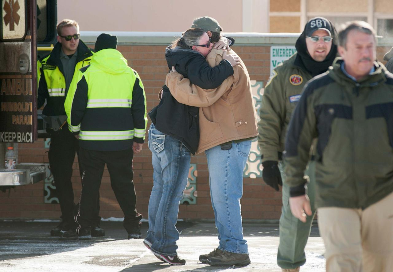 A woman hugs Chris Montes after hearing that Montes was one of the rescuers that found a family in a remote mountain range northeast of Reno, in Lovelock, Nevada, December 10, 2013. A Nevada couple and four young children reported missing on Sunday were found safe by rescue workers on Tuesday huddled in a canyon, a dispatch supervisor for the Pershing County Sheriff's Office said. Montes said the group was stranded after their truck rolled over but that they were doing well and were in good spirits when he found them. REUTERS/James Glover (UNITED STATES - Tags: SOCIETY DISASTER)
