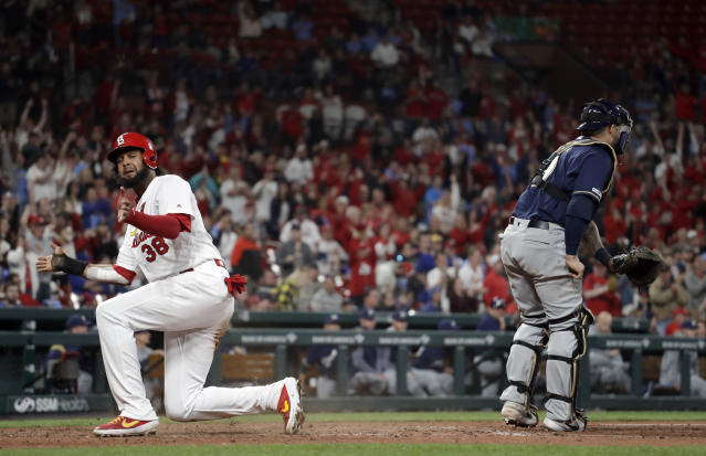 St. Louis Cardinals' Jose Martinez celebrates after scoring past Milwaukee Brewers catcher Manny Pina, right, during the eighth inning of a baseball game Tuesday, April 23, 2019, in St. Louis. (AP Photo/Jeff Roberson)