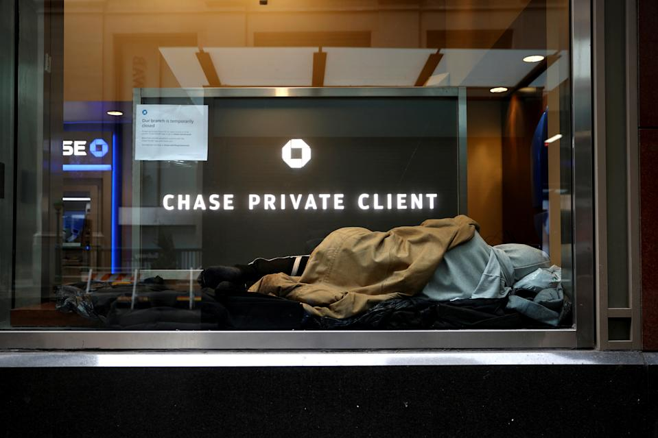 A homeless man sleeps in a closed Chase bank branch on a nearly deserted Wall Street in the financial district in lower Manhattan during the outbreak of the coronavirus disease (COVID-19) in New York City, New York, U.S., April 3, 2020. REUTERS/Mike Segar     TPX IMAGES OF THE DAY