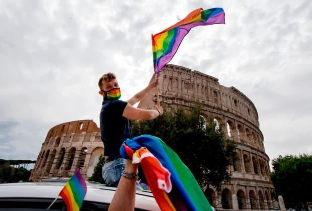 A man waves a Pride flag past the Colosseum during a Rome Pride flash mob on June 13, 2020 in Rome. Lifelines for LGBTyouth in Italy and elsewhere in Europe are thinly stretched amid the COVID-19 pandemic. (Tiziana Fabi/AFP via Getty Images - image credit)