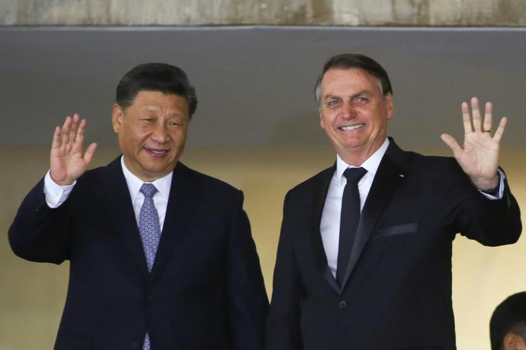 China's President Xi Jinping (L) and Brazil's President Jair Bolsonaro wave before a bilateral meeting in Brasilia ahead of a summit of the BRICS countries (AFP Photo/Sergio LIMA)