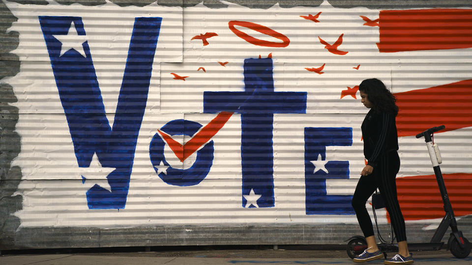 A woman walks past a voting sign painted on a wall Monday, Nov. 2, 2020, in the Venice Beach section of Los Angeles. (Jae C. Hong/AP)