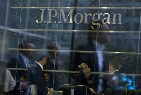 File photograph of workers reflected in the windows of the Canary Wharf offices of JP Morgan in London