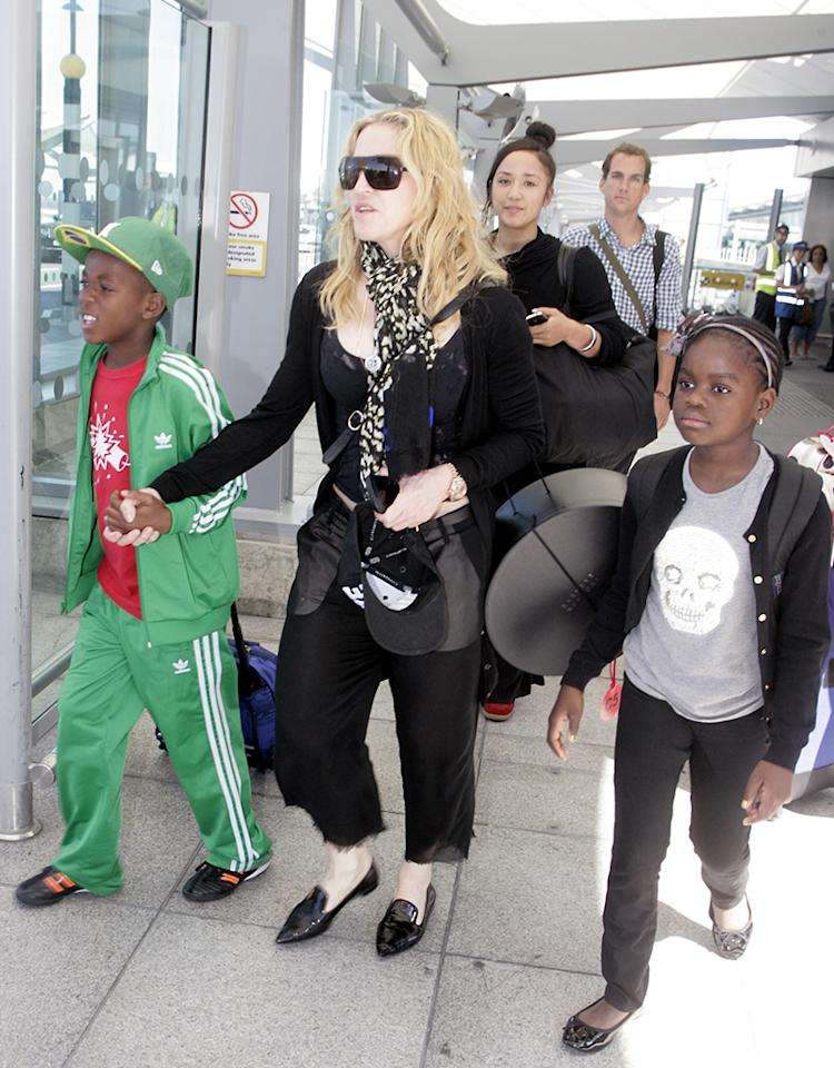 "Across the pond on the same day, fellow single mom Madonna escorted half of her brood <span style=""font-size:11.0pt;font-family:'Calibri', 'sans-serif';"">–</span> son David and daughter Mercy <span style=""font-size:11.0pt;font-family:'Calibri', 'sans-serif';"">–</span> through London's Heathrow Airport after touching down there on Friday. (7/19/2013) <br>"