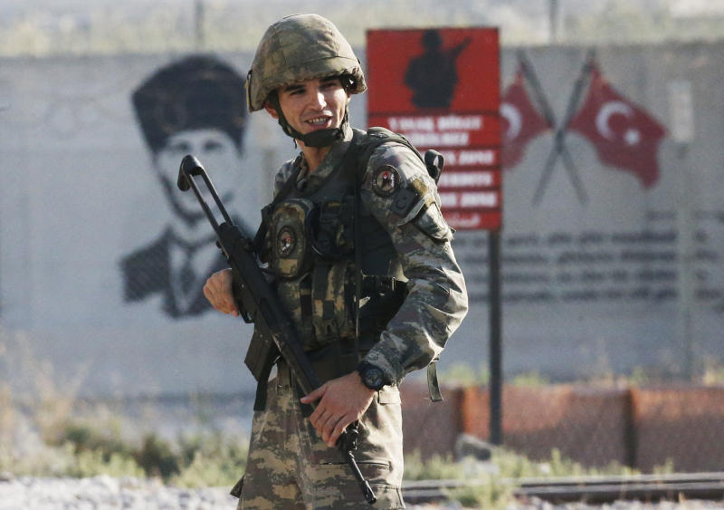 FILE-In this Wednesday, Oct. 9, 2019 file photo, shortly after the Turkish operation inside Syria had started, a Turkish soldiers stands at the border with Syria in Akcakale, Sanliurfa province, southeastern Turkey.  Since Turkey announced its incursion into neighbouring Syria to clear out Kurdish fighters last week, patriotic sentiment has run high, with signs of the glory days of the Ottoman Empire among the outward signs of patriotism. (AP Photo/Lefteris Pitarakis, File)