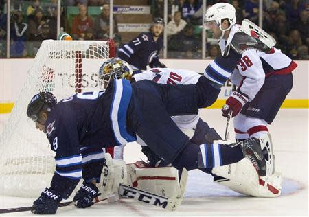 Winnipeg Jets Evander Kane (L) is tripped up by Washington Capitals goalie Branden Holtby in the first period of their NHL pre-season hockey game in Belleville Ontario September 14, 2013. REUTERS/Fred Thornhill