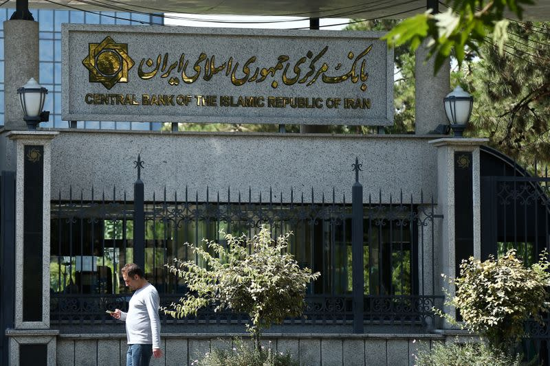 FILE PHOTO: A man walks past the Central bank of Iran in Tehran