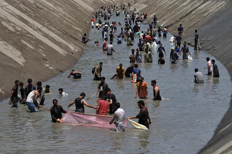 Amid the steep rise of Covid-19 cases across J&K, Kashmiri men without maintaining social distancing are fishing after Lower Jhelum Hydroelectric Project (LJHP) was shut for cleaning of accumulated heavy trash in Gantamulla area of Baramulla, Jammu and Kashmir, India on 07 June, 2020. (Photo by Nasir Kachroo/NurPhoto via Getty Images)