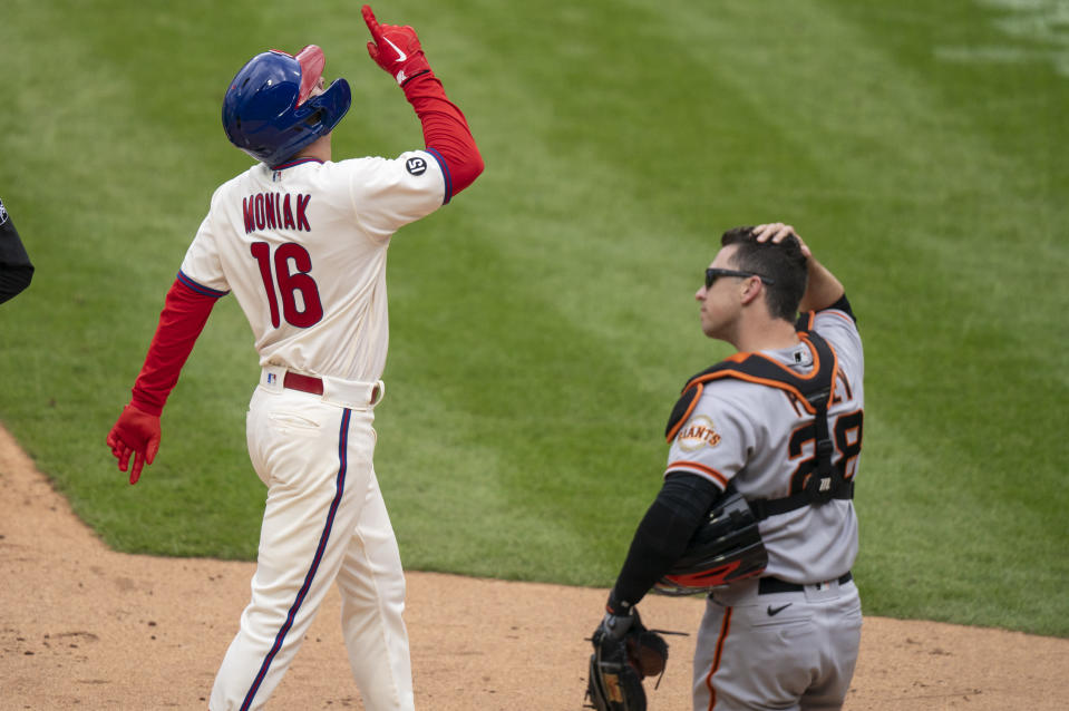 Philadelphia Phillies' Mickey Moniak, left, reacts to his three-run home run as San Francisco Giants catcher Buster Posey, right, looks on during the second inning of a baseball game, Wednesday, April 21, 2021, in Philadelphia. (AP Photo/Chris Szagola)