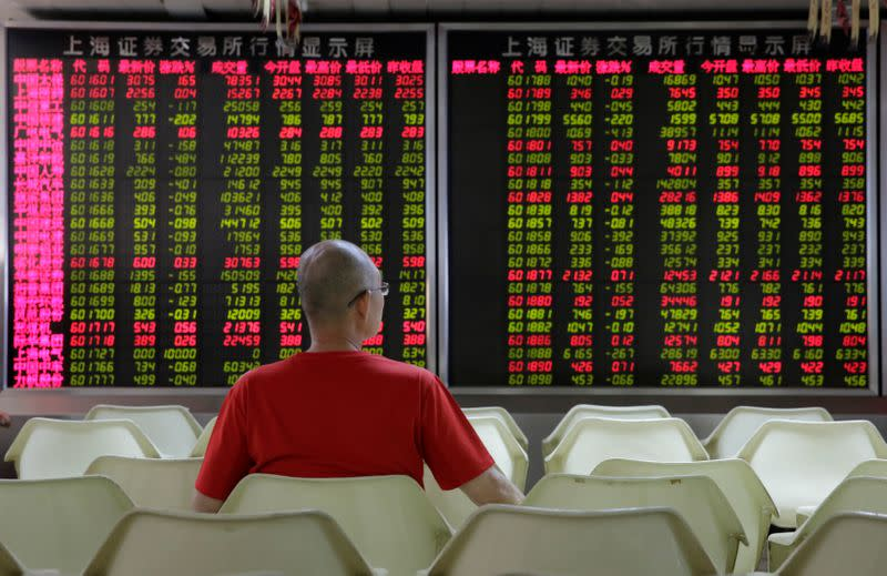 An investor watches stock prices at a brokerage office in Beijing