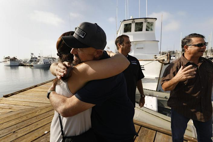 Two people hug on a pier.