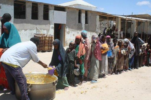 Somali children receive food ration at a feeding center in the southern Mogadishu district of Howlwadag in April