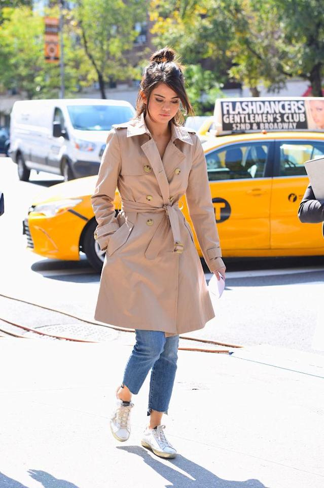 <p>Switching to a lighter color palette, Gomez returned to set in a khaki trench coat over light jeans and white sneakers. (Photo: Getty Images) </p>