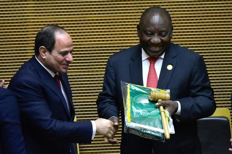 Handover: Outgoing AU chair Egyptian President Abdel Fattah al-Sisi, left, passes the baton to South African President Cyril Ramaphosa. Ramaphosa says settling the conflicts in Libya and South Sudan will be a priority of his tenure