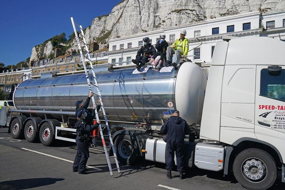 Police officers remove two protesters from the top of a tanker (Gareth Fuller/PA) (PA Wire)