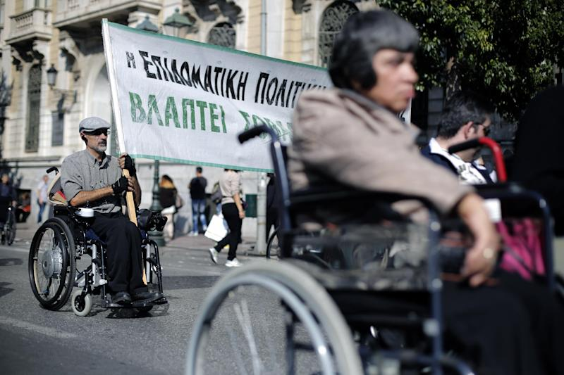 """A man on a wheelchair holds a banner reading in Greek """"State benefit policy harms our health"""" takes part in an anti-austerity demonstration in central Athens, on Thursday, Oct. 31, 2013. Athens' streets were clogged by four separate protests Thursday ahead of an inspection due to start next week by bailout lenders who are demanding fresh cuts. (AP Photo/Petros Giannakouris)"""
