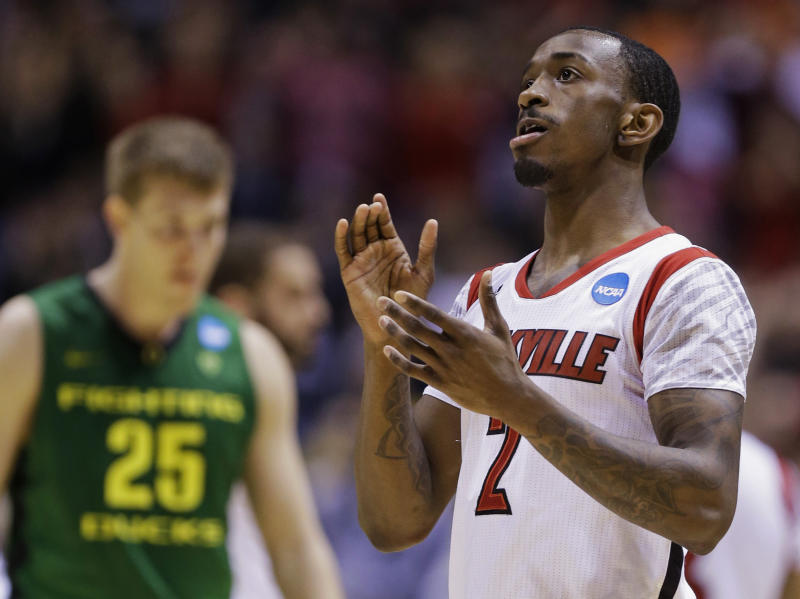 Louisville guard Russ Smith (2) reacts after his team's 77-69 win over Oregon in a regional semifinal against Oregon in the NCAA college basketball tournament, Friday, March 29, 2013, in Indianapolis. At left is Oregon's E.J. Singler (25). (AP Photo/Michael Conroy)