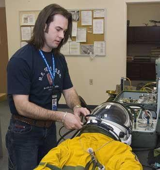 NASA life support engineering technician Joshua Graham performs a pre-flight inspection of a pressure suit.