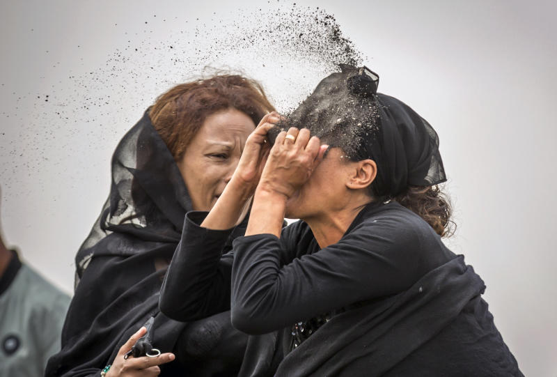 An Ethiopian relative of a crash victim throws dirt in her own face after realising that there is nothing physical left of her loved one, as she mourns at the scene where the Ethiopian Airlines Boeing 737 Max 8 crashed shortly after takeoff on Sunday killing all 157 on board, near Bishoftu, south-east of Addis Ababa, in Ethiopia Thursday, March 14, 2019. About 200 family members of people who died on the crashed jet stormed out of a briefing with Ethiopian Airlines officials in Addis Ababa on Thursday, complaining that the airline has not given them adequate information. (AP Photo/Mulugeta Ayene)
