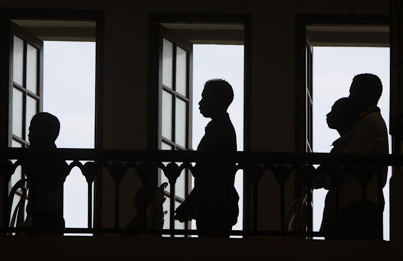 East Timorese man stand by windows as they pray during a Mass at a cathedral in Dili, East Timor on Sunday, March 18, 2012. East Timor voted for a new president Saturday in an election that tested the young nation's political stability ahead of the planned departure of U.N. troops later this year. (AP Photo/Firdia Lisnawati)