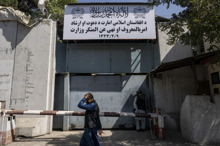 """An Afghan man walks past the former Women's Affairs Ministry building in Kabul, Afghanistan, Saturday, Sept. 18, 2021. Afghanistan's new Taliban rulers set up a ministry for the """"propagation of virtue and the prevention of vice"""" in the building that once housed the Women's Affairs Ministry, escorting out World Bank staffers Saturday as part of the forced move. (AP Photo/Bernat Armangue)"""