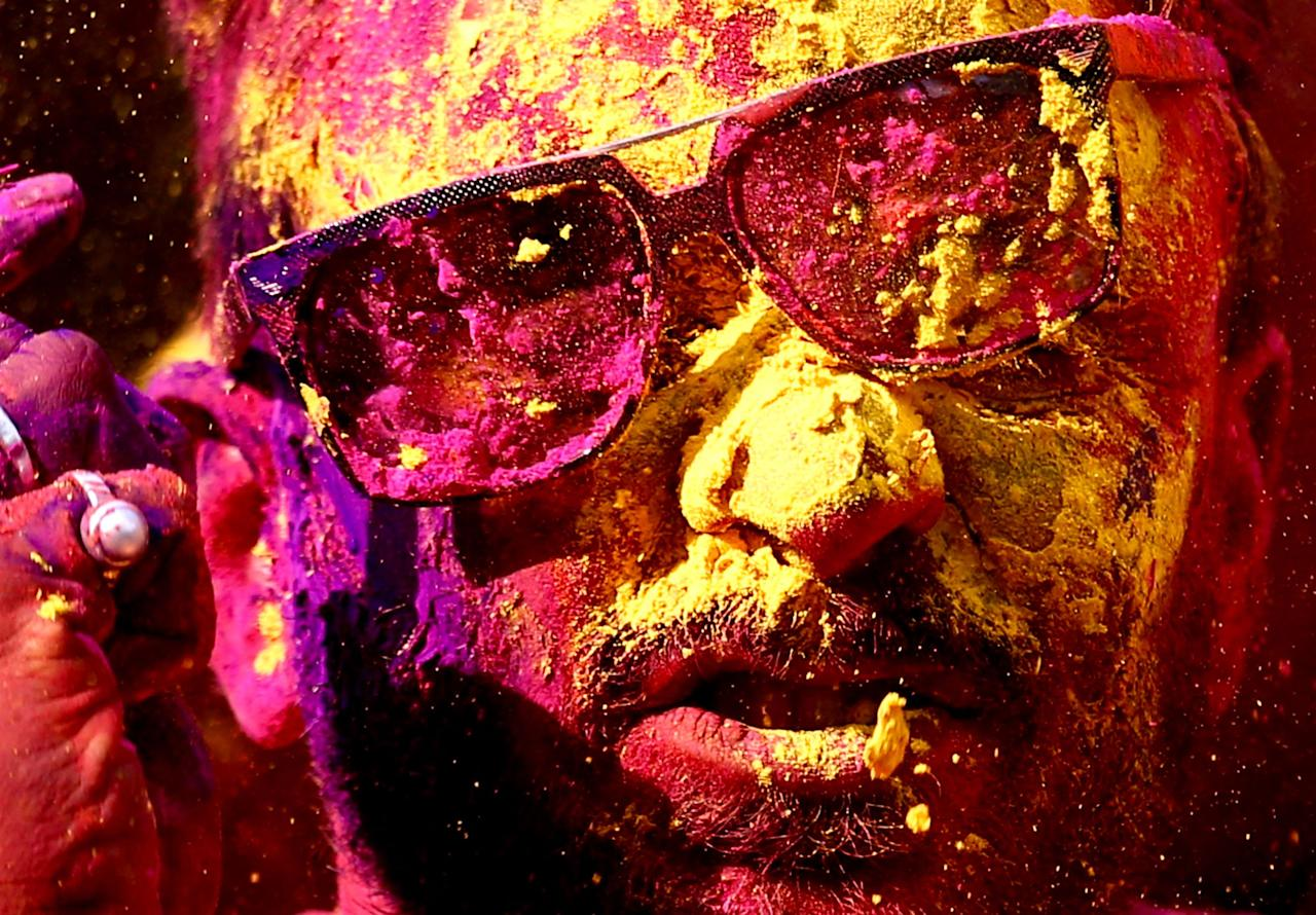 <p>An Indian reveller covered with powdered colors celebrates the Holi festival in Bangalore, India, 13 March 2017. The Holi festival is celebrated on the last full moon day of the lunar month Phalguna and heralds the onset of the spring season. (Jagadeesh NV/EPA) </p>
