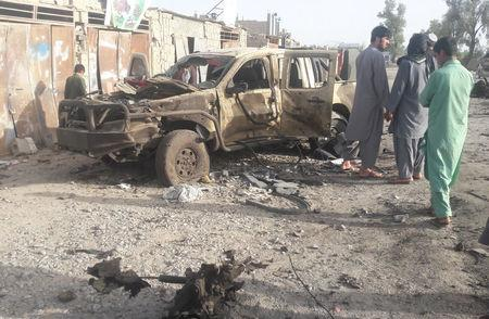 Residents look at an Army vehicle which was damaged during battle between Afghan security forces and Taliban in Farah