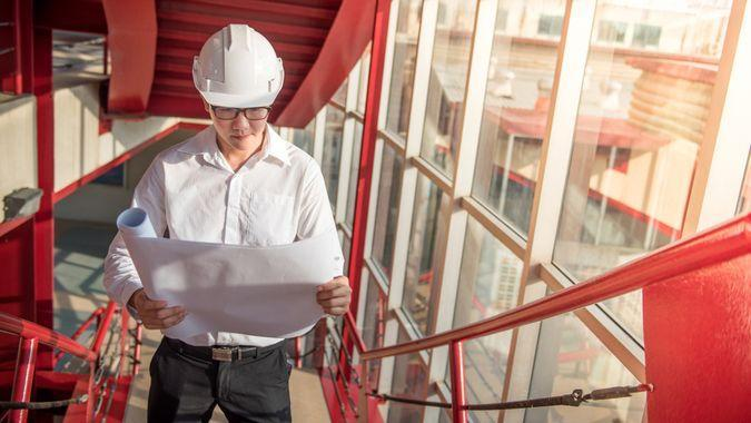 Engineer or Architect checking architectural drawing while wearing a personal protective equipment safety helmet at construction site.