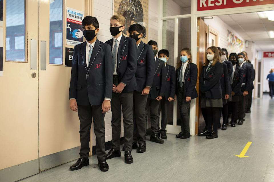 Year eight pupils wear face masks as a precaution against the transmission of the novel coronavirus as they queue in a corridor before attending an English lesson at Moor End Academy in Huddersfield, northern England on September 11, 2020. - Millions of children across England have returned to school after the Covid-19 lockdown with many schools introducing measures to enable as safe an environment as possible. (Photo by OLI SCARFF / AFP) (Photo by OLI SCARFF/AFP via Getty Images)