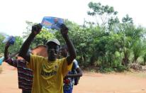 Supporters of politician Serge Bruno Mageot, hold his campaign posters ahead of the upcoming elections in Bimbo 3, suburbs of Bangui
