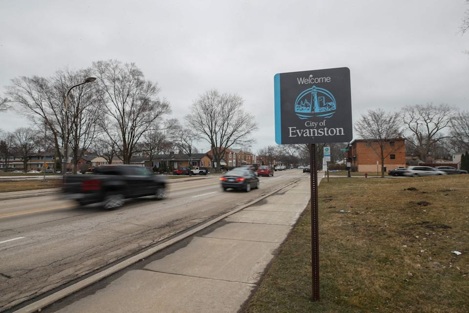 Cars drive past a sign welcoming people to the city of Evanston, Illinois.