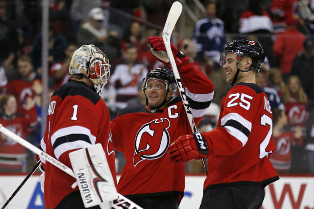 New Jersey Devils goaltender Keith Kinkaid (1) celebrates with Devils' Mirco Mueller (25) and Devils' Andy Greene after defeating the Dallas Stars in an NHL hockey game Tuesday, Oct. 16, 2018, in Newark, N.J. (AP Photo/Adam Hunger)