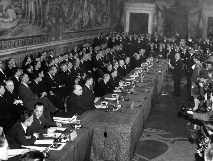FILE - In this March 25, 1957 file photo, then Mayor of Rome Umberto Tupini, standing at center right, addresses delegates of six west European Nations; France, Germany, Italy, Belgium, The Netherlands and Luxembourg, gathered inside the Oriazi and Curiazi Hall of Rome's Campidoglio Capitoline Hill to sign a treaty establishing the European Economic Community (EEC). Eleven months after Britain's formal departure from the EU, Brexit becomes a fact of daily life on Friday, Jan. 1, 2021. Brexit marks the end of an awkward relationship. Britain joined the then-European Economic Community in 1973, but never fully embraced the bloc's project of ever-closer integration. (AP Photo, Files)
