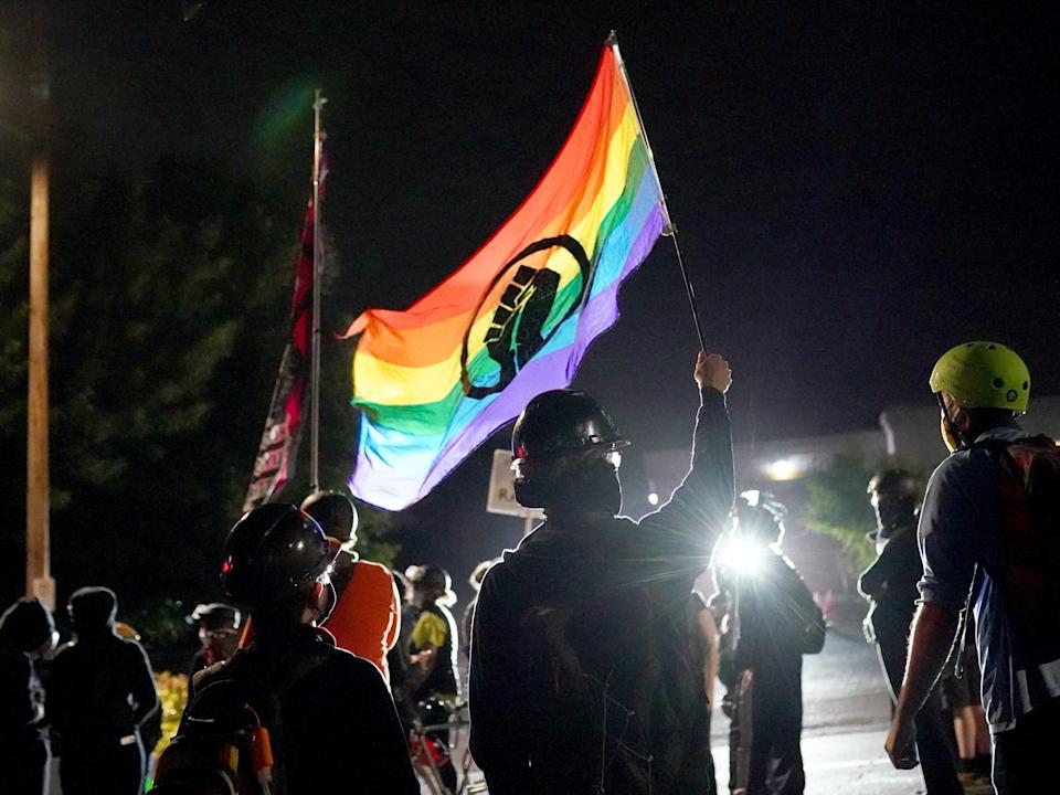 """Protesters chant and wave flags in front of the Multnomah County Sheriff's Office on August 11, 2020 in Portland, Oregon. <p class=""""copyright"""">Nathan Howard/Getty Images</p>"""